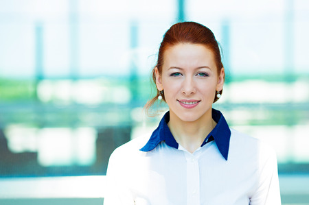 headshot: Closeup headshot portrait, young beautiful business woman in white shirt smiling isolated on corporate office windows background. Positive human emotions, facial expressions, attitude, life perception Stock Photo
