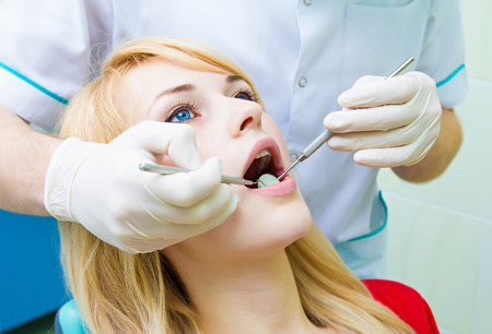 thorough: Closeup portrait young female, woman, patient sitting in dentist chair, office, wide open mouth getting oral thorough examination, procedure done by doctor isolated background clinic office, equipment
