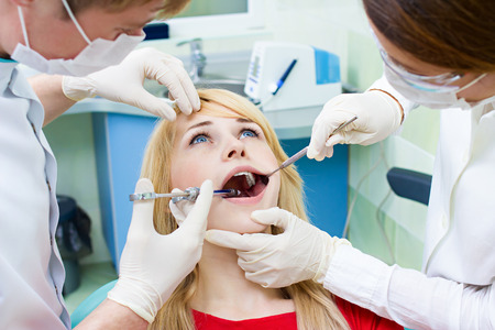 Closeup portrait young female, woman patient sitting in dentist chair, office with wide open mouth getting painful anesthetic injection done by doctor, his assistant isolated background clinic office photo