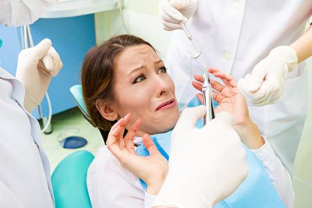 クローズ アップ肖像若い訪問歯科椅子に立地、恐れ、変な格好で怖いおびえる女の子女性は歯科プロシージャ歯抽出分離クリニック事務所背景の掘