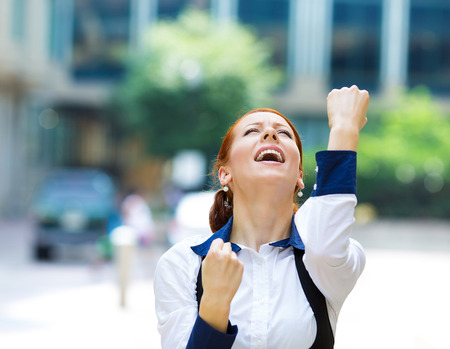 job satisfaction: Closeup portrait happy smiling business woman with arms up, excited pumping fists, celebrating isolated background outdoors corporate office. Positive human emotion, facial expression feeling reaction Stock Photo