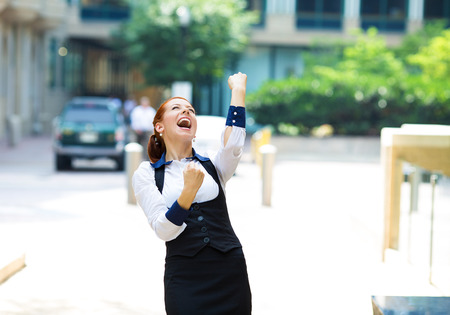 Closeup portrait happy smiling business woman with arms up, excited pumping fists, celebrating isolated background outdoors corporate office. Positive human emotion, facial expression feeling reaction photo