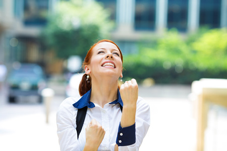 job satisfaction: Closeup portrait happy smiling business woman with arms up, excited pumping fists, celebrating isolated background outdoors corporate office.