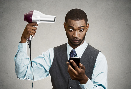 Closeup portrait worried, shocked business man, deal maker reading bad news on smart, mobile phone holding hairdryer isolated black grey background. Human face expression, emotion, corporate executive photo