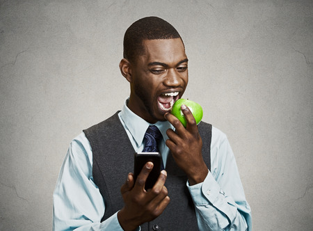 Closeup portrait serious business man, deal maker reading bad news on smart, mobile phone holding, eating green apple isolated black grey background. Human face expression, corporate executive emotion photo
