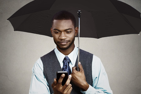 Closeup portrait skeptical business man reading bad news on smart, mobile phone holding umbrella protected from rain isolated black grey background. Human face expression, emotion, corporate executive photo