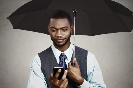 business skeptical: Retrato del primer esc�ptico hombre de negocios la lectura de las malas noticias en el paraguas de tel�fonos inteligentes, el holding m�vil protegido de la lluvia aislada negro fondo gris. La expresi�n del rostro humano, emoci�n, ejecutivo de una empresa