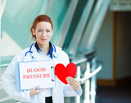 under pressure: Closeup portrait happy smiling female health care professional, woman family doctor, cardiologist with stethoscope holding heart, blood pressure sign isolated hospital hallway background. Patient plan Stock Photo
