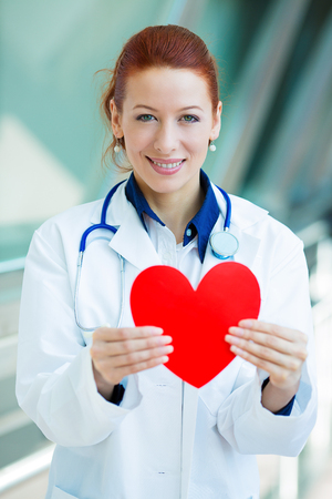 metabolic: Closeup portrait happy smiling female health care professional, woman family doctor cardiologist, nurse with stethoscope holding red heart, isolated hospital hallway background. Patient plan, visit