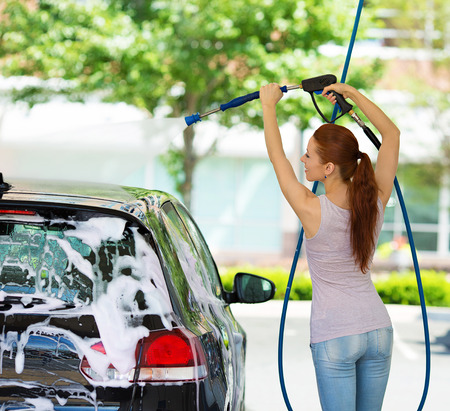 portrait of young, smiling, happy, attractive woman washing automobile at manual car washing self service station