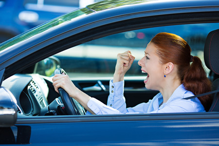 Closeup portrait of displeased angry pissed off aggressive woman driving car, shouting at someone photo