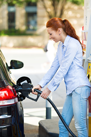 refuel: Portrait of happy smiling pretty, attractive woman filling compact car tank with petrol at gas station