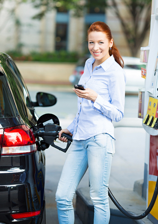 fueling: Portrait of happy smiling pretty, attractive woman filling compact car tank with petrol at gas station