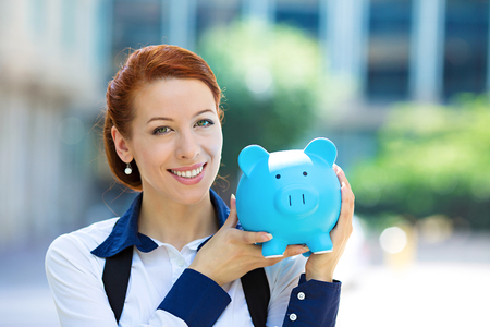 creditor: Closeup portrait of happy, smiling business woman, bank employee holding piggy bank Stock Photo
