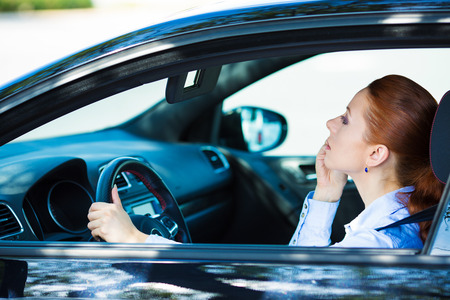 endangering: Closeup portrait dangerous irresponsible young, female driver applying her makeup using rear view mirror as she drives to work endangering herself, other motorists by her inattention. Traffic concept Stock Photo