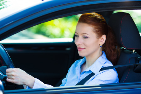 Portrait smiling, attractive brunette woman, buckled up, driving, testing her new black car, automobile, purchased at dealership, isolated street, city traffic background. Safe driving habits concept photo