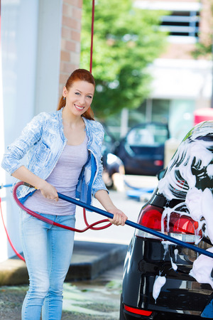 pressured: Picture, portrait young, smiling, happy, attractive woman washing automobile at manual car washing self service station, cleaning with foam, pressured water. Transportation, auto, vehicle care concept Stock Photo