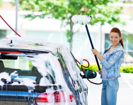 water transportation: Picture, portrait young, smiling, happy, attractive woman washing automobile at manual car washing self service station, cleaning with foam, pressured water. Transportation, auto, vehicle care concept Stock Photo