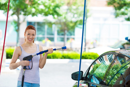 washing car: Picture, portrait young, smiling, happy, attractive woman washing automobile at manual car washing self service station, cleaning with foam, pressured water. Transportation, auto, vehicle care concept Stock Photo