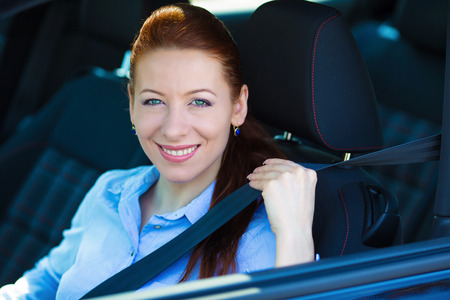 seatbelt: Closeup portrait young smiling, happy, attractive woman pulling on seatbelt inside black car. Driving safety, buckle up to prevent traffic death, accidents concept. Save life