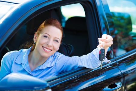 Close-up portret gelukkig, het glimlachen, jonge, aantrekkelijke vrouw, koper zitten in haar nieuwe zwarte auto met sleutels geïsoleerd stad straat dealerschap veel achtergrond. Persoonlijk vervoer, auto aankoop begrip Stockfoto