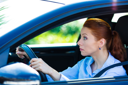 stay alert: Closeup portrait sleepy, tired, fatigued, exhausted young woman falling asleep, trying to stay alert while driving her car after long hour trip, isolated street background. Transportation, sleep Stock Photo