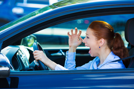 displeased: Closeup portrait displeased angry pissed off aggressive woman driving car, shouting at someone, hands up in air isolated traffic background. Emotional intelligence concept. Negative human expression Stock Photo