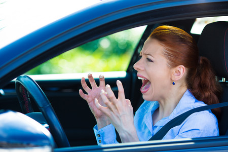 Closeup portrait displeased angry pissed off aggressive woman driving car, shouting at someone, hands up in air isolated traffic background. Emotional intelligence concept. Negative human expression Stock Photo