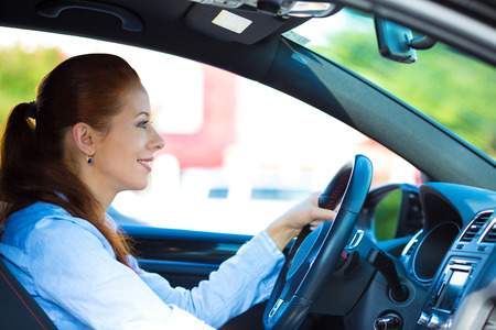 buckled: Portrait smiling, attractive brunette woman, buckled up, driving, testing her new black car, automobile, purchased at dealership, isolated street, city traffic background. Safe driving habits concept