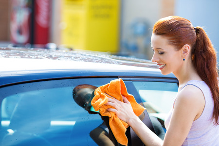 business cloth: Closeup picture, image young woman, driver, dry wiping  her car with microfiber cloth after washing it