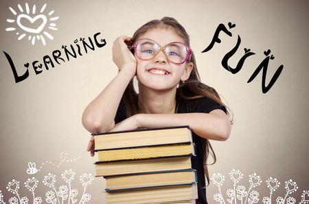 Closeup portrait cute, smiling, happy, little girl with glasses, sitting in front of pile books, isolated dark grey background. Childhood education concept. Face expressions, emotions, life perception Stock Photo