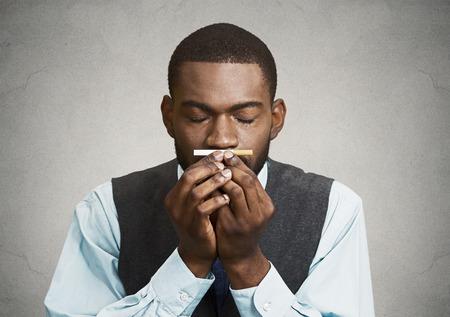 human health: Primer retrato, headshot, joven apuesto hombre de negocios, ejecutivo corporativo, hombre de aspecto gracioso, cigarrillo craving, tabaco, aislado negro fondo gris. Malo, peligroso concepto de h�bitos de salud humana