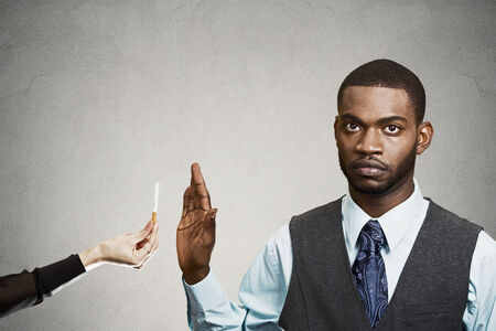 quitting: Closeup portrait, headshot handsome young business man says no to cigarette offered by person, stop hand gesture, isolated black, grey background. Healthy life choices. Human face expression, reaction Stock Photo