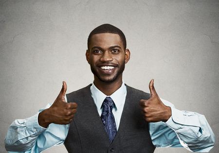 クローズ アップ肖像画ハンサムな若い笑顔ビジネス男、カメラでサインを親指を与える企業の従業員は、黒灰色の背景を分離しました。肯定的な人