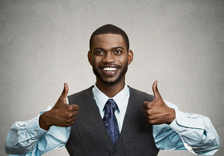 job satisfaction: Closeup portrait handsome young smiling business man, corporate employee giving thumbs up sign at camera isolated black grey background. Positive human emotions, facial expression, feelings. Symbols