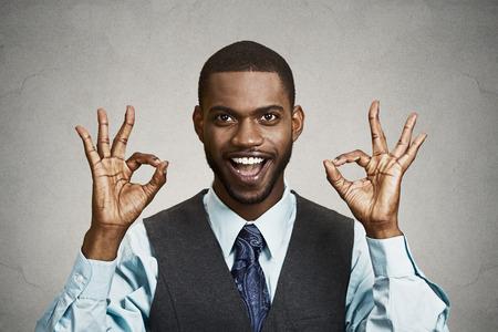 Close-up portret jonge knappe, vrolijke, glimlachen, opgewonden man, corporate werknemer, arbeider die OK teken met vingers, geïsoleerde zwarte grijze achtergrond. Positieve menselijke emotie gezichtsuitdrukkingen, symbool