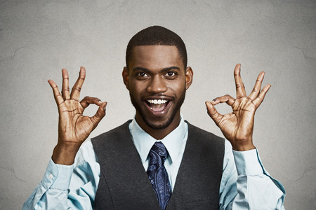 job satisfaction: Closeup portrait young handsome, happy, smiling, excited man, corporate employee, worker giving OK sign with fingers, isolated black grey background. Positive human emotion facial expressions, symbol