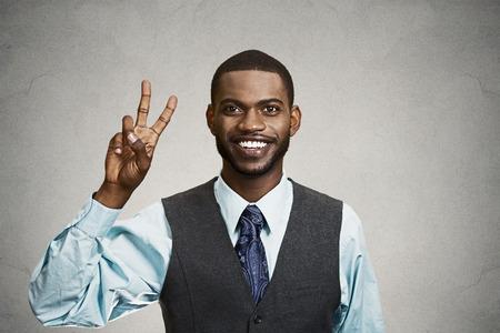 simbolo de la paz: Primer retrato, joven headshot, estudiante de la celebración de la paz, la victoria, dos signos, fondo negro aislado. La emoción positiva humana, las expresiones faciales, los símbolos, la comunicación actitud. Éxito en la vida Foto de archivo