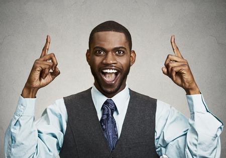 gezichts uitdrukkingen: Close-up portret jonge zakenman die omhoog wijst met idee, oplossing, waaruit met de wijsvinger nummer een, geïsoleerde zwarte grijze achtergrond. Positieve menselijke emoties, gezichtsuitdrukkingen, symbolen, teken Stockfoto