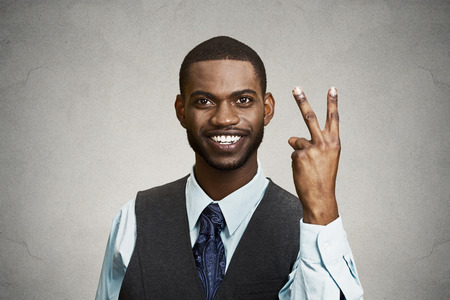 victory sign: Closeup portrait, headshot young man, student holding up peace, victory, two sign , isolated black background. Positive human emotion, facial expressions, symbols, attitude communication. Life success