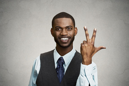 trilogy: Closeup portrait young happy, confident, handsome business man giving a three times fingers sign gesture with hands, isolated black grey background. Positive emotion facial expression feeling, symbols