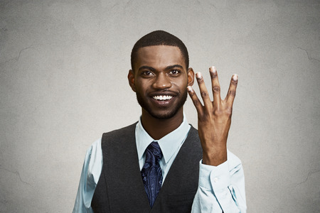 quadruple: Closeup portrait, headshot, happy, smiling young man making four times sign gesture with hand fingers, isolated black grey background. Positive emotions, facial expressions, feelings, attitude, symbol