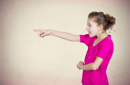 Closeup side view portrait young, excited, happy girl smiling, laughing, pointing finger towards someone gesture, isolated grey brown background. Positive human emotion, attitude, reaction perception photo