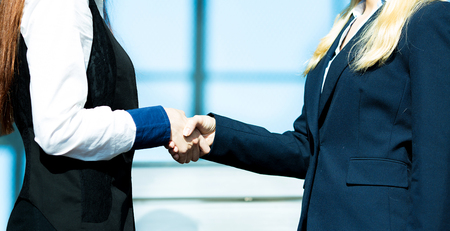 Closeup portrait happy smiling businesspeople, attractive business women shaking hands outdoor, isolated background corporate office, building background. Positive face expressions, emotions, attitude photo