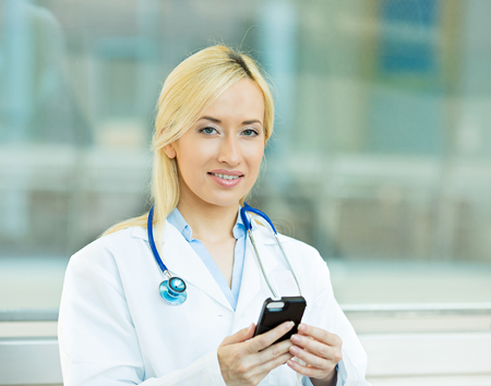 Closeup portrait young healthcare professional, doctor, nurse, dentist, researcher, physician assistant reading text sms, message on cellphone holding smart phone isolated hospital hallway  background photo