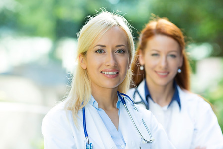 healthcare workers: Closeup portrait headshot happy, smiling female doctors, healthcare professionals isolated outdoors hospital background. Patient visit. Health care reform. Positive human face expression, emotion