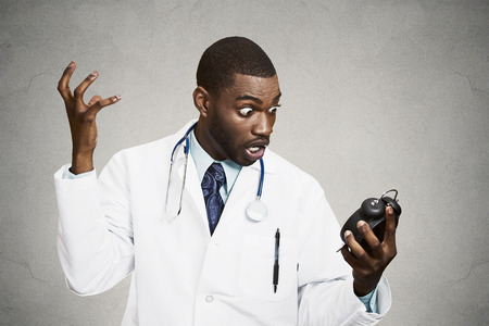 duties: Closeup portrait stressed young male doctor, health care professional nurse holding alarm clock, very unhappy, shocked, demanding pressured by time isolated black background. Negative emotion reaction Stock Photo