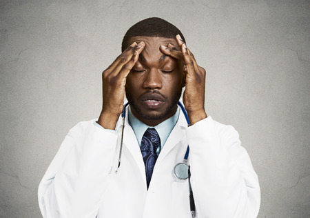 doctor burnout: Closeup portrait sad health care professional with headache, stressed, holding head with hands. Nurse, doctor with migraine overworked, overstressed isolated black background. Negative human emotions