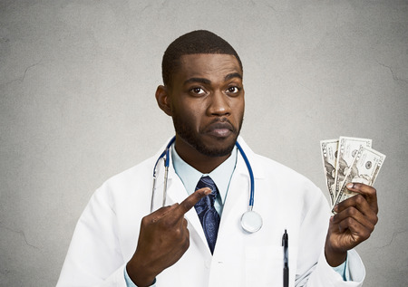 doctor holding money: Closeup portrait grumpy greedy miserly health care professional, male doctor holding, pointing at his money dollars in hand isolated black background. Negative human emotion facial expression attitude