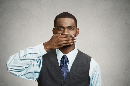 repress: Closeup portrait, silent young business man covering closed mouth observing. Speak no evil concept, isolated black background. Negative human emotion, facial expression sign symbol. Media news coverup